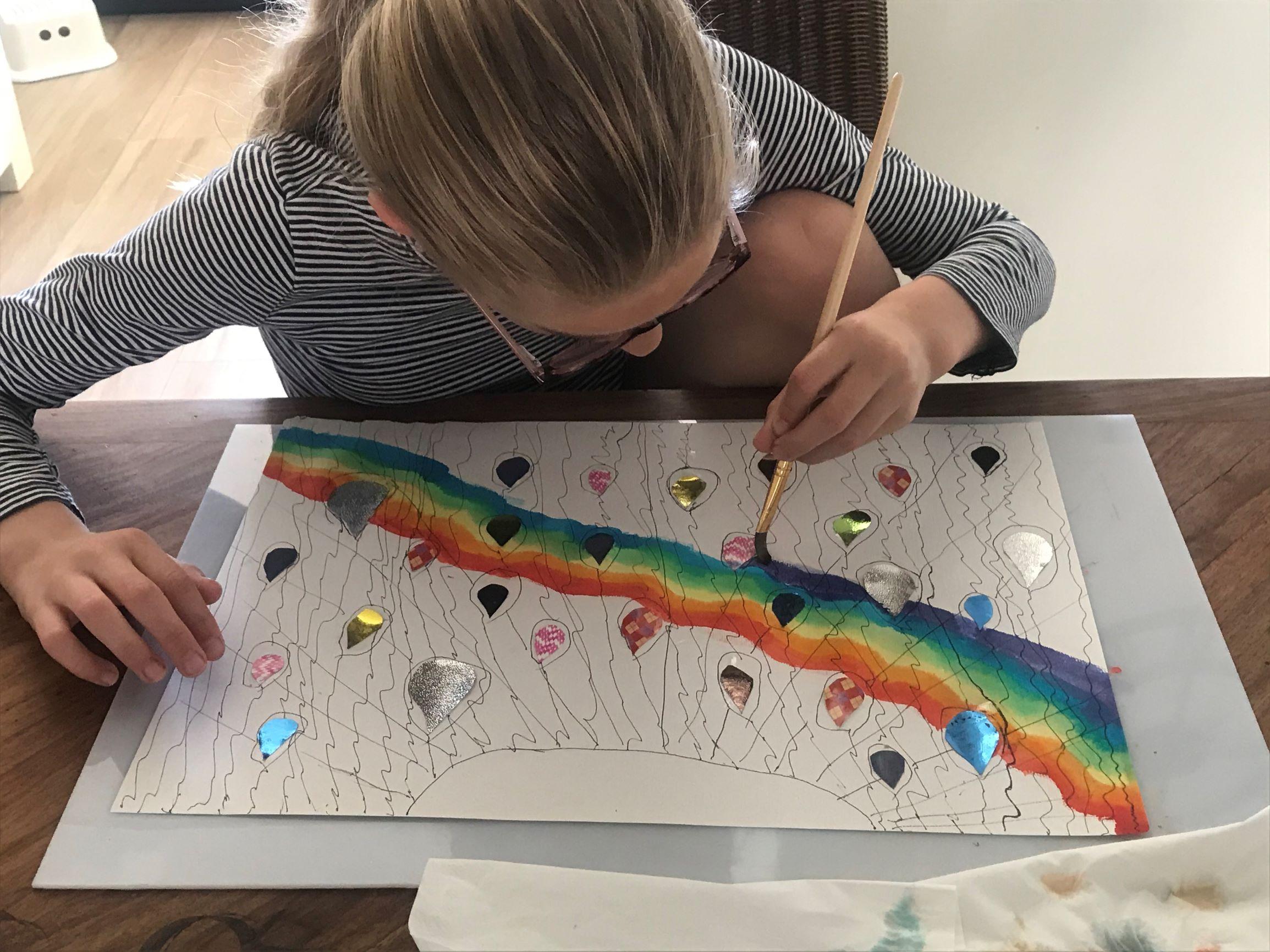 Mare kan zich creatief zo goed uiten. Hier schildert zij een regenboog van ecoline. Als ze klaar is luisteren we naar haar verhaal.